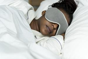A woman sleeping with a sleeping mask