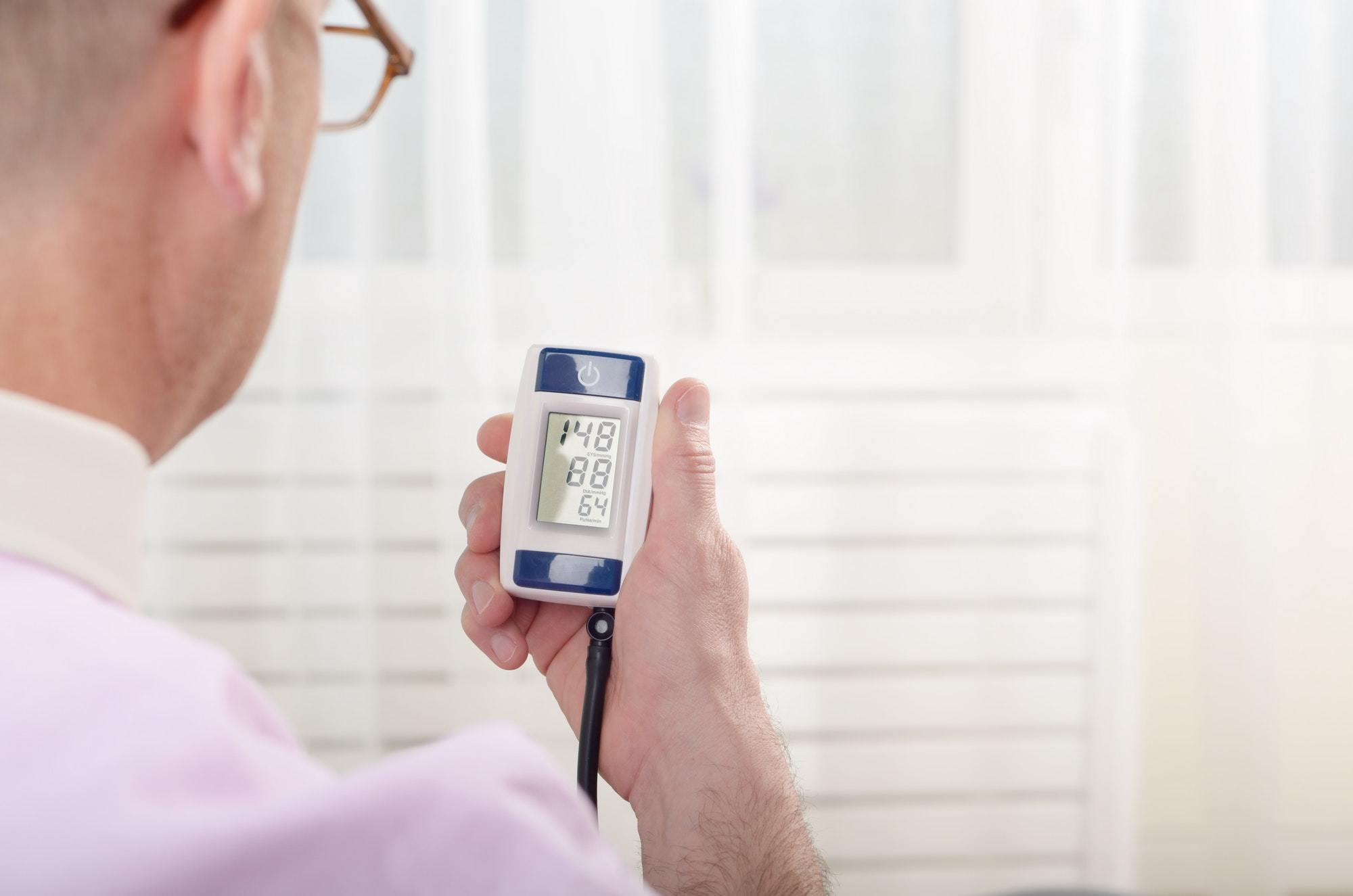 Man read measurement result from digital blood pressure monitor