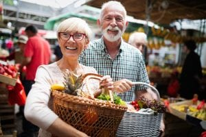 Mature couple shopping vegetables and fruits on the market. Healthy diet