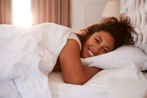 Portrait Of Woman Waking Up In Bed And Smiling At Camera