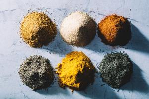 Six piles of colorful spices and herbs.
