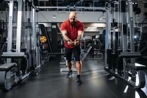 Strong athlete, training on exercise machine