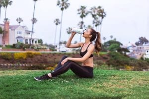 Woman drinking supplements for pre workout routine.
