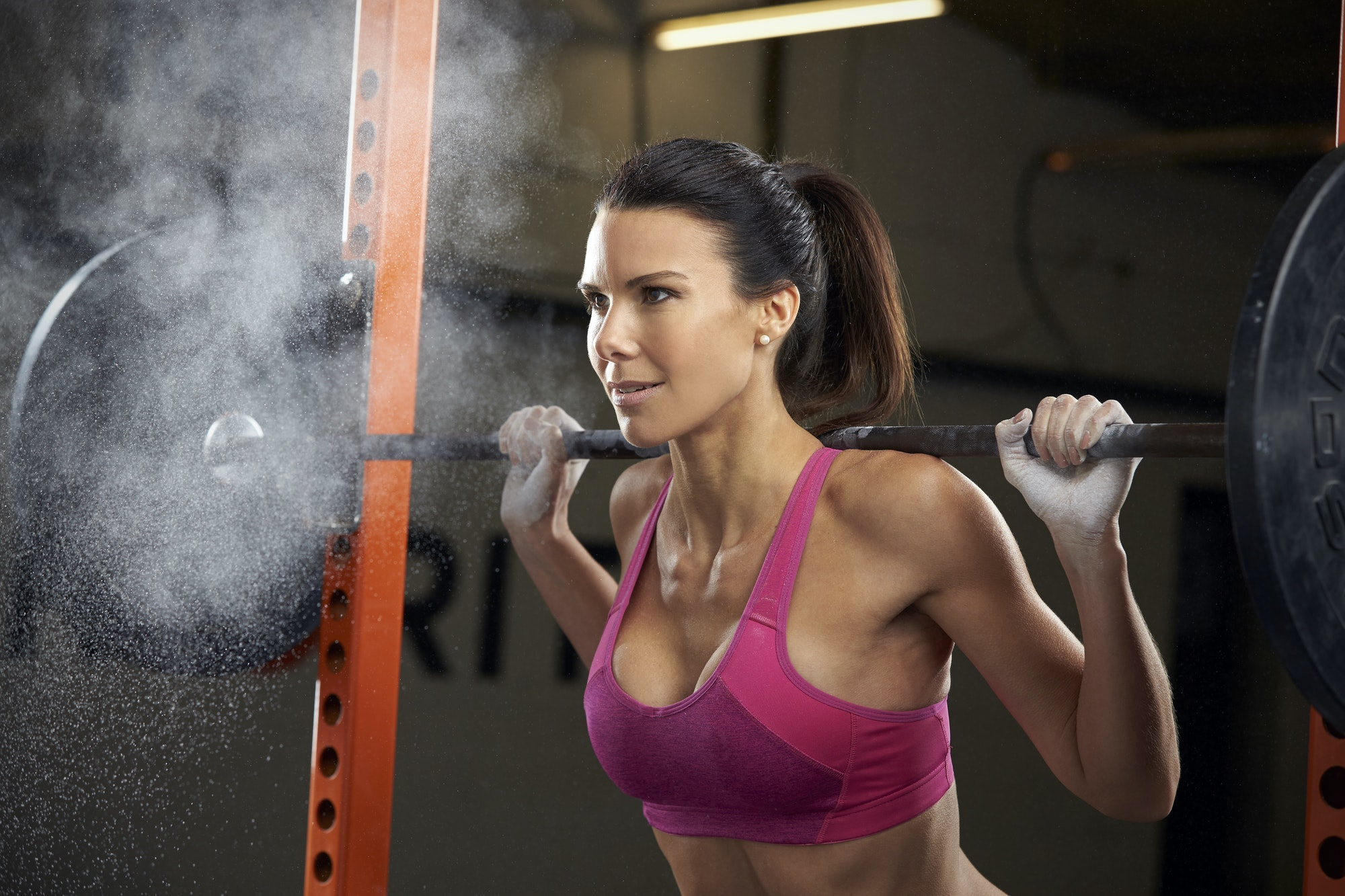 Woman In Gym Lifting Weights On Barbell